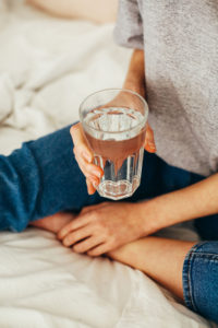 person sitting on bed holding drinking cup of water