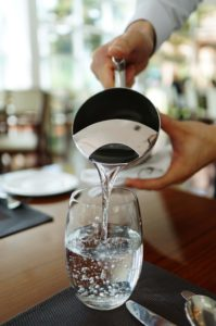server pouring water into glass from pitcher